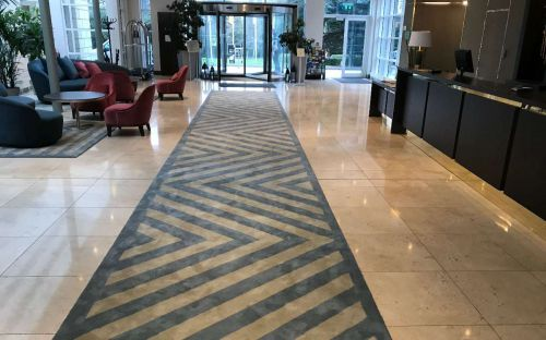Hand tufted runner with chevron design in hotel lobby