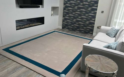 Hand tufted cream rug with teal border