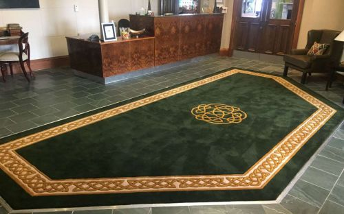 Hand tufted green rug with celtic border and motif in a hotel lobby