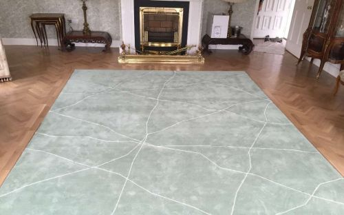 Hand tufted mint green rug with cracked white lines