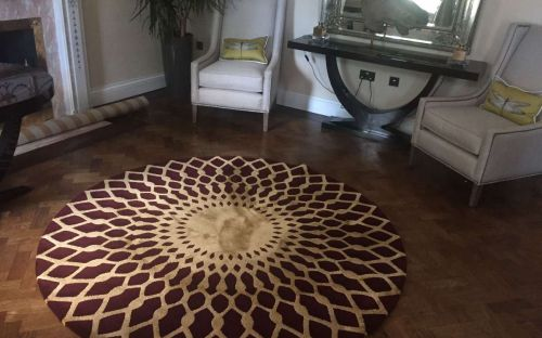 Hand tufted red circle rug with gold spirograph like design